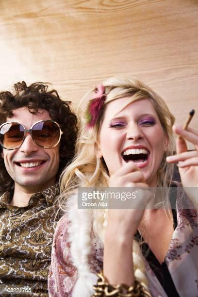Young Woman Laughing with Hippie Man Smoking Marijuana