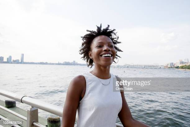 young woman laughing with hudson river in background - carefree stock pictures, royalty-free photos & images