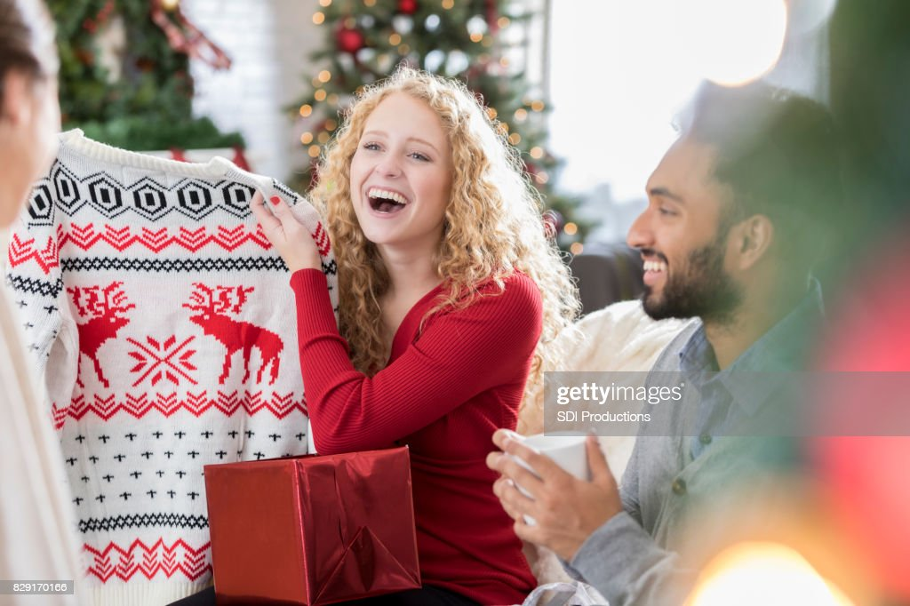 Young woman laughs after opening Christmas sweater : Stock Photo