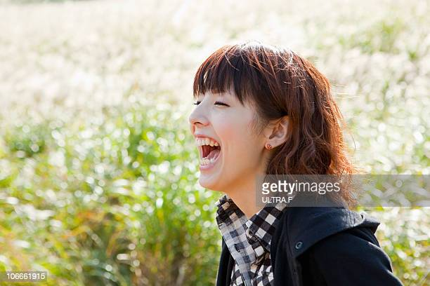 Young woman laughs at susuki grass meadow.