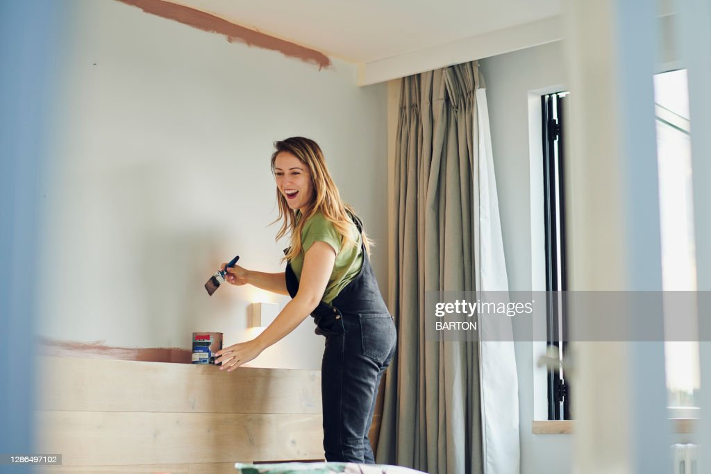 Young Woman laughs whilst painting bedroom wall : Stock Photo