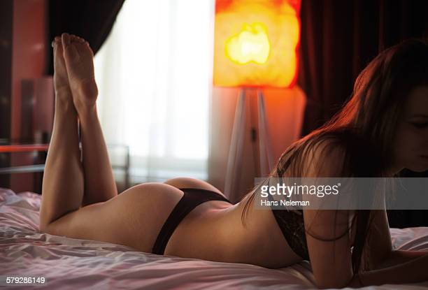 young woman laying in bed - donna seducente foto e immagini stock