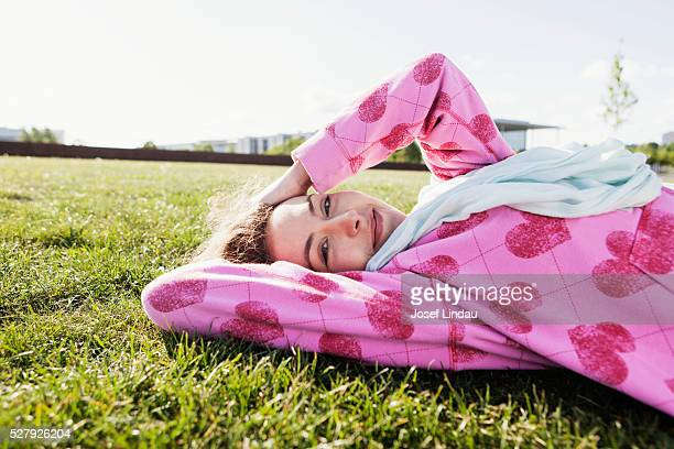 Young woman laying in park