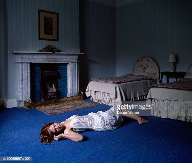 young woman laying on floor in bedroom - mulher morta imagens e fotografias de stock