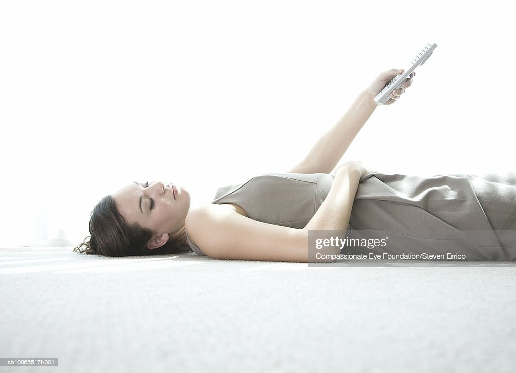 Young woman laying on floor with remote control : Stock Photo