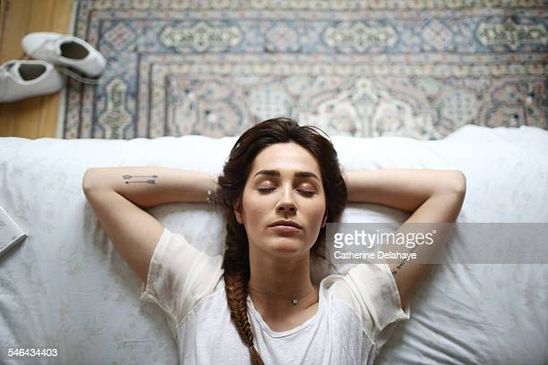a young woman laying on her bed - slapen stockfoto's en -beelden