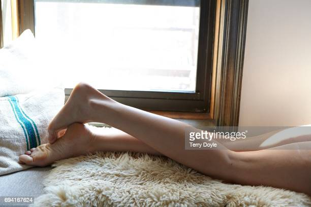young woman laying on her stomach with her legs crossed - woman lying on stomach with feet up stock photos and pictures