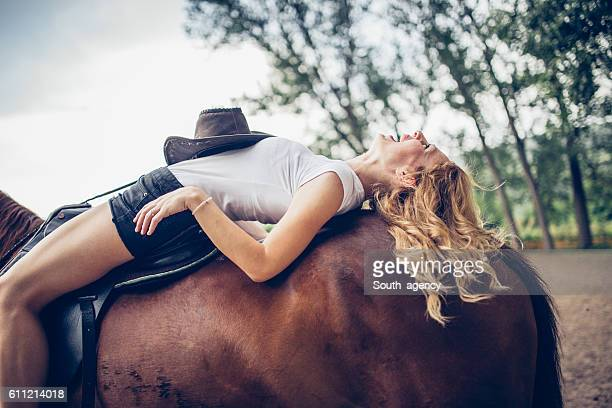 Young woman laying on horse