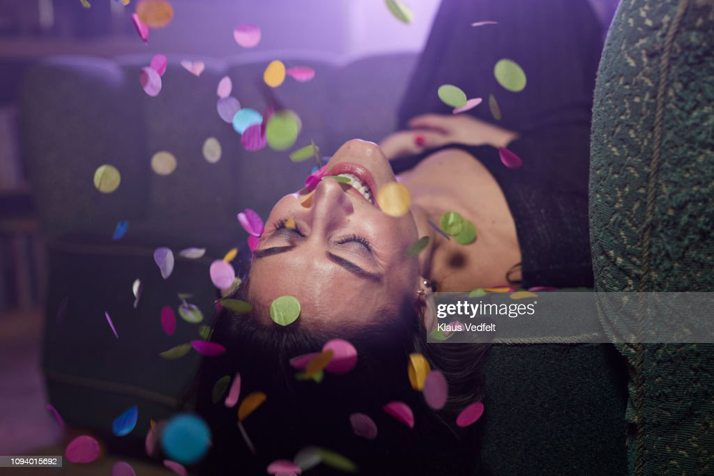 Young woman laying on sofa with confetti falling : Stock Photo