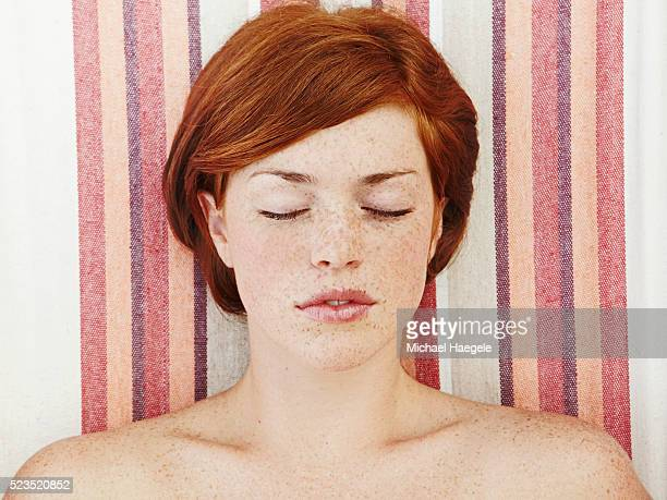young woman laying with eyes closed - そばかす ストックフォトと画像