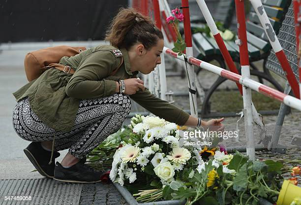 A young woman lays a candle among flowers left by mourners outside the French Embassy the day after the terror attack in Nice that has left at least...