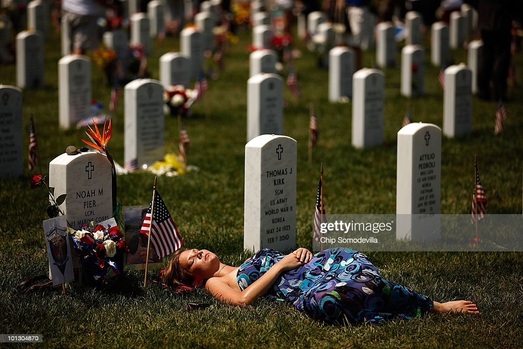 A young woman lays down on the grave of U.S. Marine Corps Lance Corporal Noah Pier on Memorial Day at Arlington National Cemetery May 31, 2010 in Arlington, Virginia. Pier was killed Feburary 12, 2010 in Marja, Afghanistan. This is the 142nd Memorial Day observance at the cemetery.