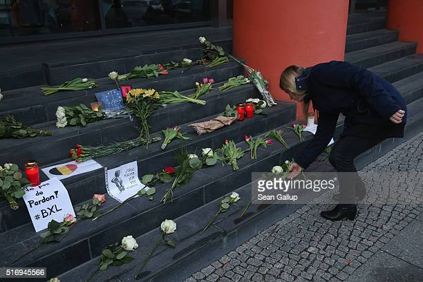 A young woman lays flowers at the steps of the Belgian Embassy following today's terrorist attacks in Brussels on March 22 2016 in Berlin Germany The...