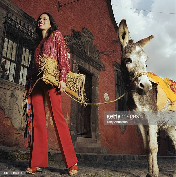 Young woman leading donkey along street