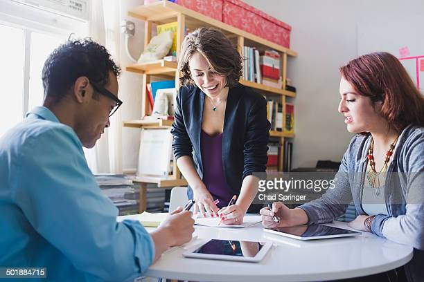 Young woman leading small meeting