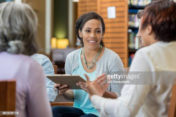 young woman leads university study group session - college professor stock photos and pictures