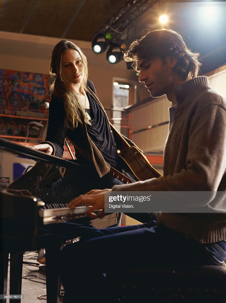 Young Woman Leaning Against a Piano as She Watches a Man Playing : Stock Photo
