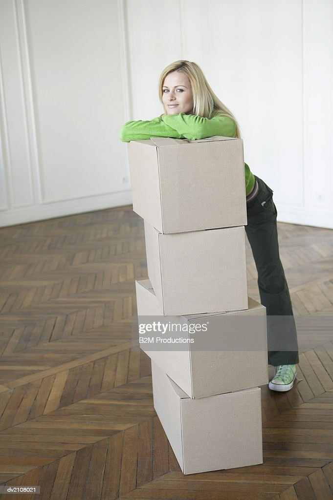 Young Woman Leaning Against a Stack of Cardboard Boxes in an Empty Room : Stock Photo