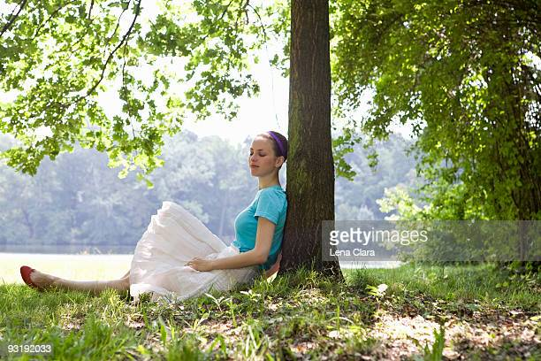 A young woman leaning against a tree next to a lake