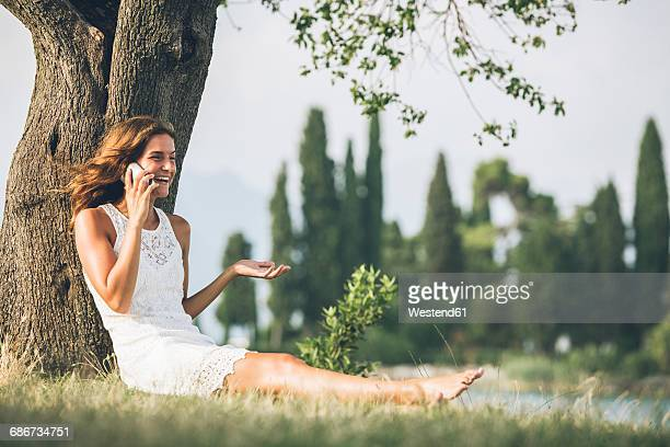 Young woman leaning against a tree talking on cell phone