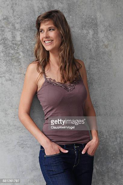young woman leaning against a wall - sonnig stock pictures, royalty-free photos & images