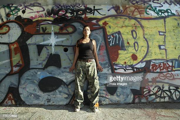young woman leaning against a wall - junge frau allein stock-fotos und bilder