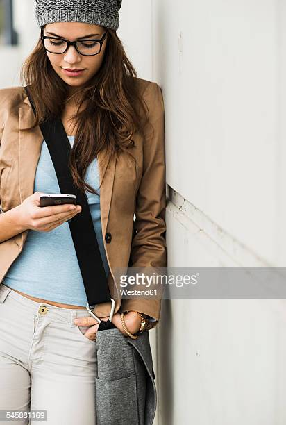 young woman leaning against a wall reading sms - mani in tasca foto e immagini stock