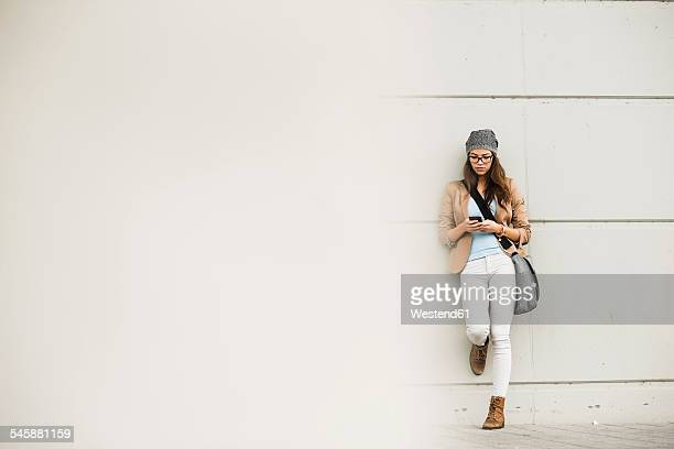 Young woman leaning against a wall waiting