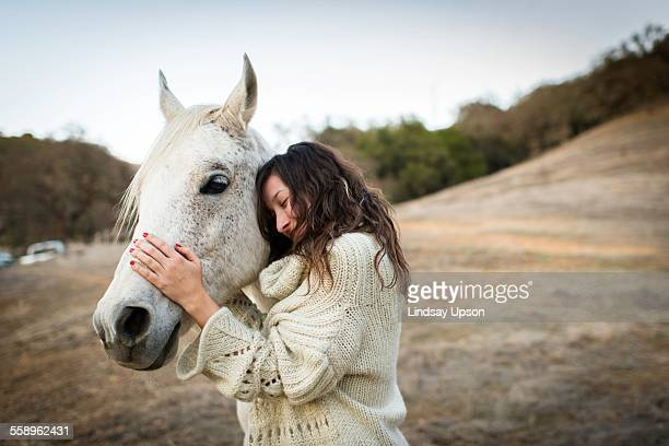 young woman leaning against and petting white horse in field - 1 woman 1 horse fotografías e imágenes de stock