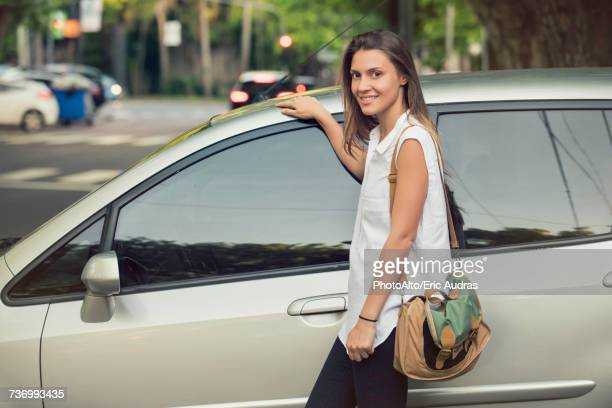Young woman leaning against car, smiling