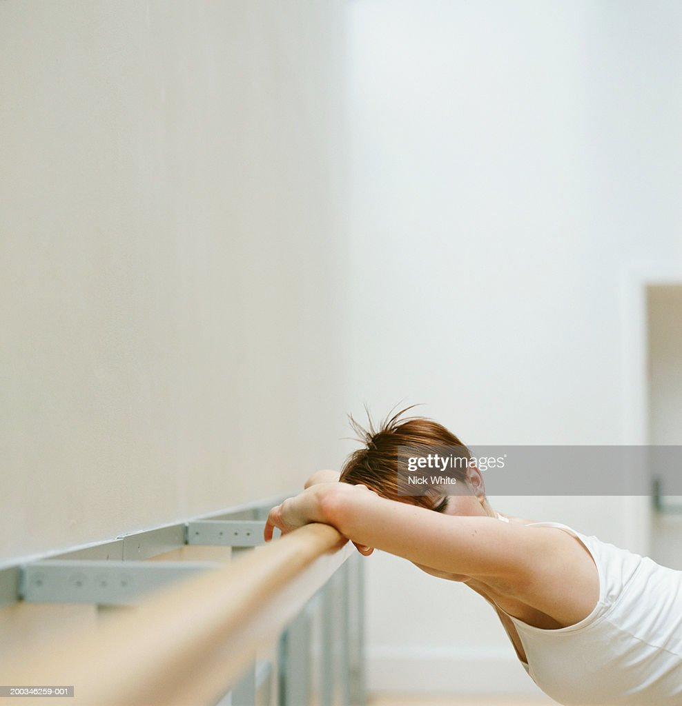 Young woman leaning against rail in dance studio, stretching : Stock Photo