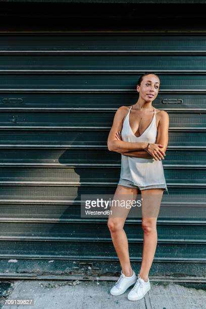 Young woman leaning against roller shutter with wrms crossed
