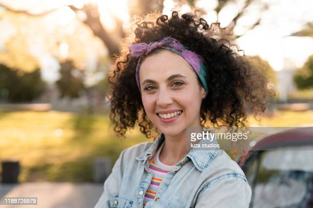 young woman leaning against the hood of her car - headband stock pictures, royalty-free photos & images