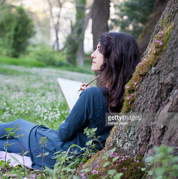 young woman leaning against tree, drawing