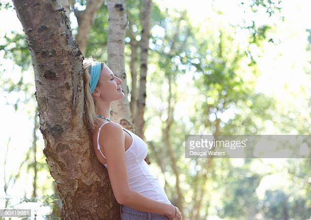 Young woman leaning against tree in forest.