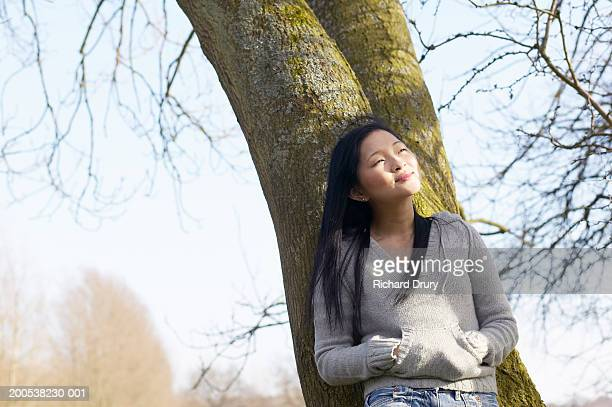 Young woman leaning against tree in park, smiling, eyes closed