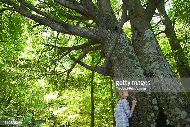 Young woman leaning against tree, looking up