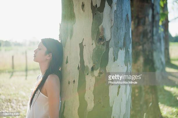 Young woman leaning against tree trunk