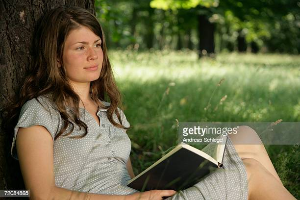 young woman leaning against tree with a book - girls open legs stock photos and pictures