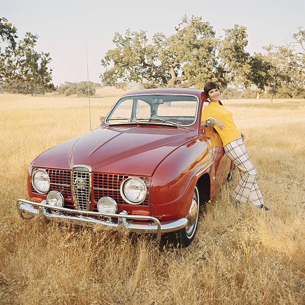 Young woman leaning against vintage car