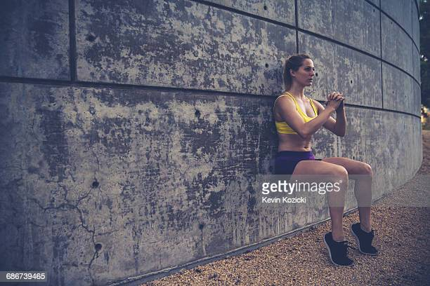 'Young woman leaning against wall outdoors, doing squats'