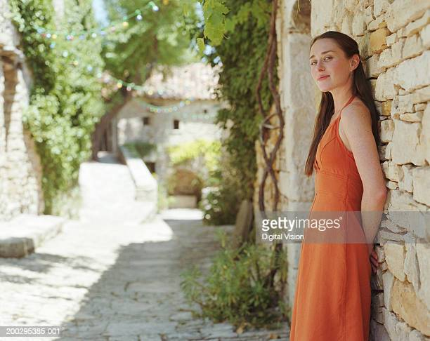 young woman leaning against wall outdoors, smiling, portrait - orange dress stock pictures, royalty-free photos & images