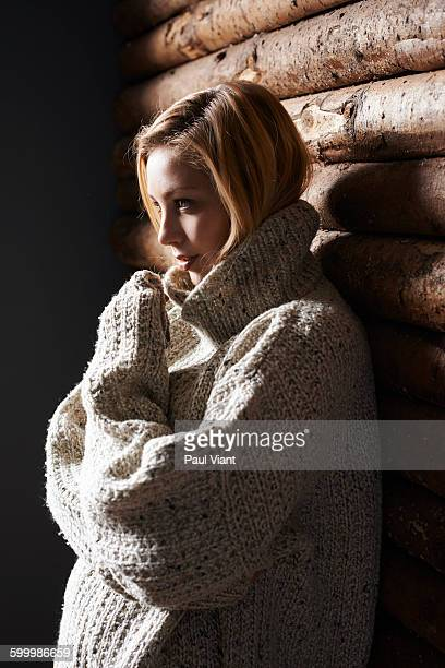 young woman leaning against wood panelled wall