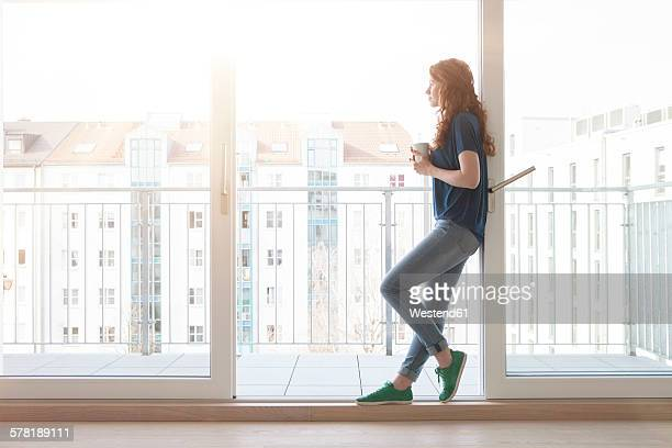 young woman leaning at sliding door of balcony looking at distance - apartment balcony stock pictures, royalty-free photos & images