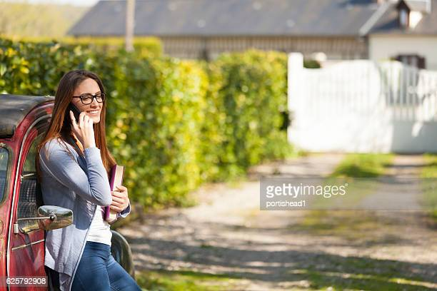 Young woman leaning back on car and talking on phone