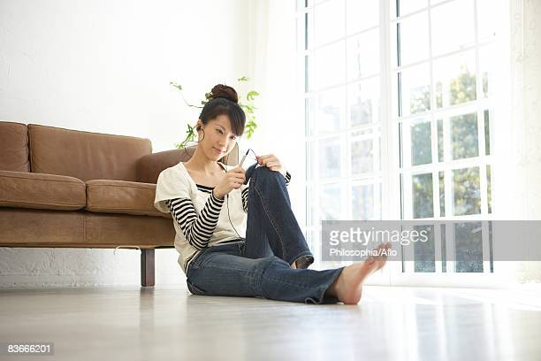 Young woman leaning by sofa and listening music