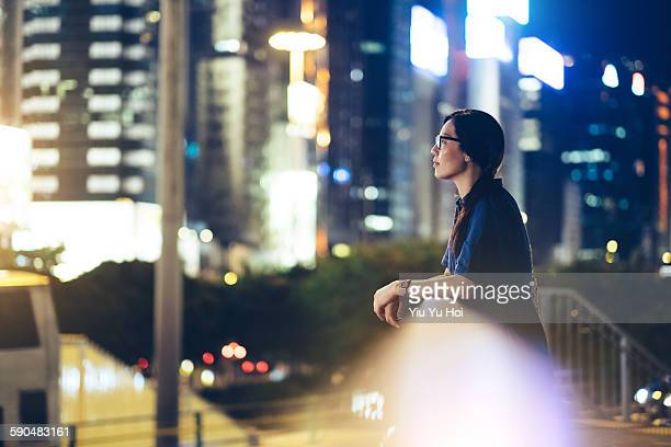 Young woman leaning by the fence looking over city
