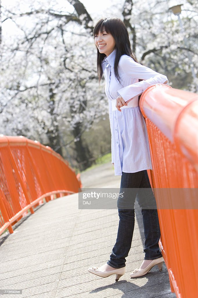 Young Woman Leaning on a Rail, Side View, Differential Focus : Photo