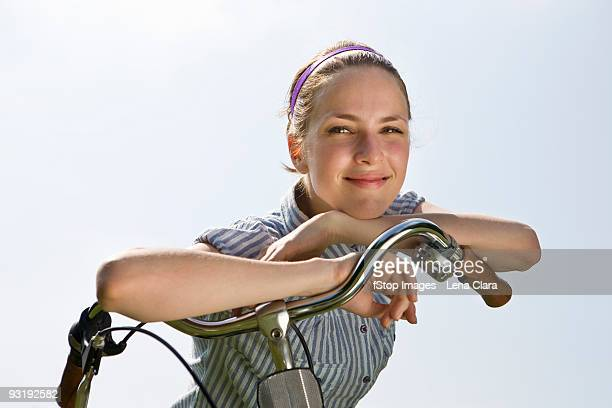 A young woman leaning on bicycle handlebars
