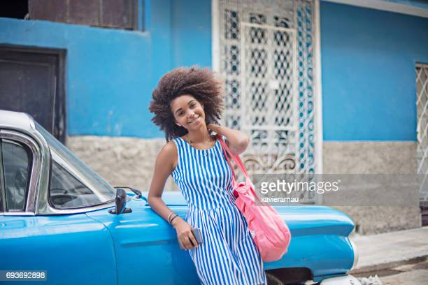 Young woman leaning on blue taxi in city